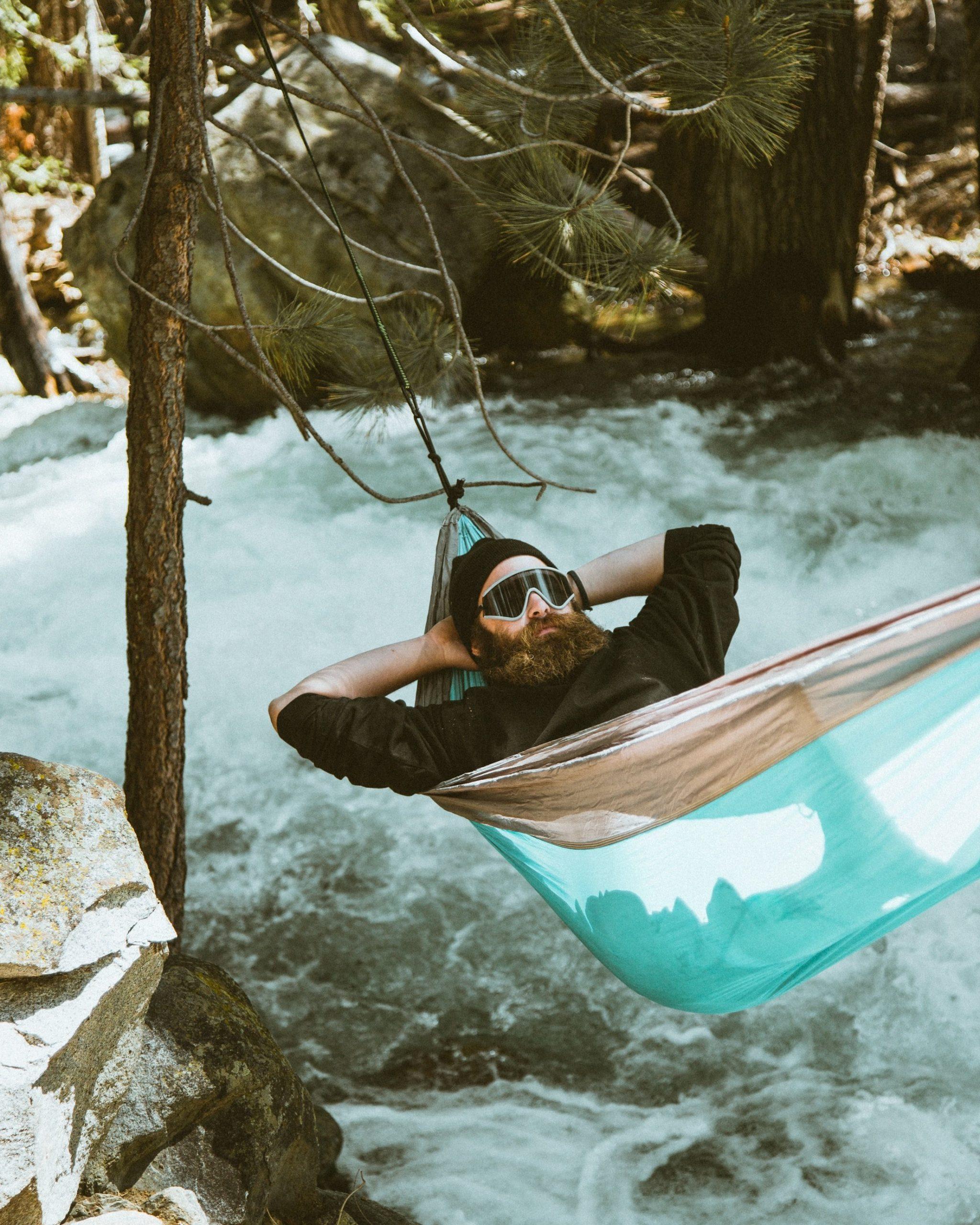 Man sleeping in hammock over water